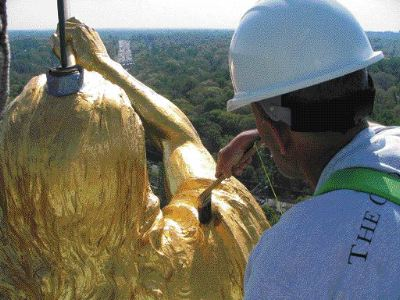 Dennis Da Silva smooths a layer of gold onto the statue Moroni at the Mormon temple in Kensington.