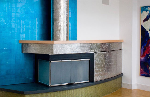 Blue Glass Wall - This fireplace surround is gilded with a hand tinted silver leaf from Japan.